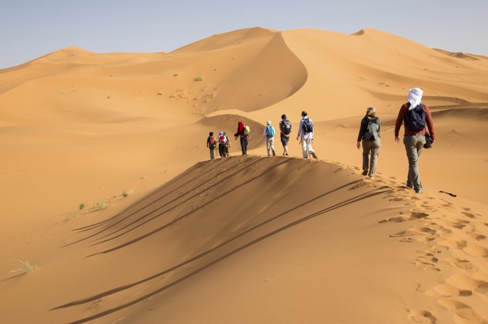 Group of people walking on sand dunes. Long shadows on the left side.